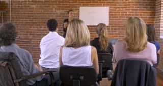 Motivational speaker businesswoman getting audience feedback participation at a training seminar or business brainstorming sessions while writing on a white board
