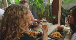 Multi ethnic group of attractive women laughing and having fun in a restaurant or bar pub with food and drinks