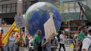 NEW YORK CITY, UNITED STATES - SEPTEMBER 21, 2014 - Protestors pulling a rotating earth at the People's Climate March, a large-scale activist event to advocate global action against climate change.