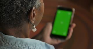 Older attractive senior black woman in her 50s or 60s looking at her smart phone technology with a chroma key green screen - OTS rack focus
