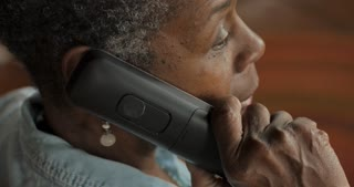 Older black woman in her 50s or 60s with short black and gray hair talking on a cordless landline phone - OTS
