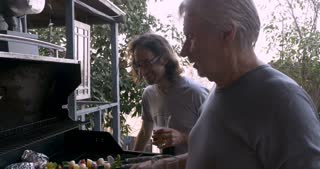 Older father and son grilling vegetable shish kebabs on a barbecue together while talking and spending time together