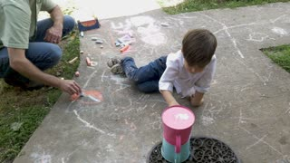 Overhead of a young 4 - 5 year old boy helping an adult man color with chalk on a sidewalk