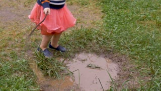 Overhead of a young girl splashing around in a mud puddle in a skirt in slow motion outside