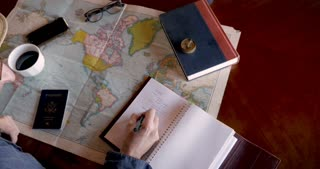 Overhead of hipster man planning a travel trip of a lifetime with a map writing his bucket list in a journal