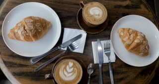 Overhead of two cups of coffee and two pastries from a bakery on a breakfast table