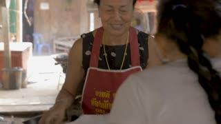 PAK NAM, CHUMPHON, THAILAND - CIRCA FEB 2017 - Friendly happy smiling Thai woman produce vendor hands a plastic bag of vegetables to a customer in a local wet market