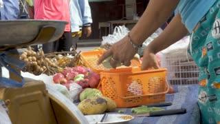 PAK NAM, CHUMPHON, THAILAND - CIRCA FEB 2017 - Thai woman giving Thai baht cash change to a customer at an outdoor produce stand
