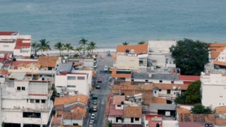 Pan of the ocean and beach above the old historic city of Puerto Vallarta Mexico
