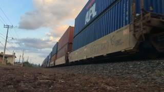 PATZCUARO , MEXICO - CIRCA JULY 2016 - A freight train carrying shipping containers moving along railroad tracks during sunrise or sunset