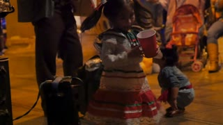 PATZCUARO, MEXICO - SEPTEMBER 15 2016 - Adorable little girl wearing a red green and white dress dancing and drinking out of a plastic cup during Mexican Independence day