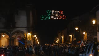 PATZCUARO, MEXICO - SEPTEMBER 15 2016 - Green white and red Viva Mexico sign illuminated at night during Mexican Independence day celebration with a large crowd of people walking the streets