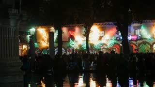 PATZCUARO, MEXICO - SEPTEMBER 15 2016 - Mexican building decorated with the colors of Mexico during Mexican Independence Day with a large group of people celebrating in the plaza and their reflection in a fountain at night