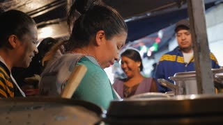 PATZCUARO, MEXICO - SEPTEMBER 15 2016 - Mexican women serving street food in a Pozeleria to hungry happy customers at night on the street