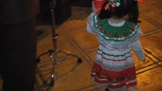 PATZCUARO, MEXICO - SEPTEMBER 15 2016 - Two small children dancing and drinking next to a live Mexican band performing during Mexican Independence Day