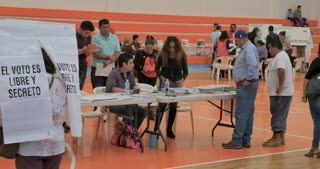 PATZCUARO, MICHOACAN, MEXICO - JULY 1, 2018 - Mexican male voter receives his ballot after checking in at the voting station on election day