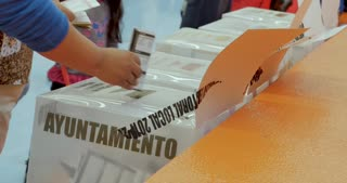 PATZCUARO, MICHOACAN, MEXICO - JULY 1, 2018 - Mexican voters put their completed ballots into the voting boxes to be counted for the official voting tally of the presidential election