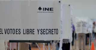 PATZCUARO, MICHOACAN, MEXICO - JULY 1, 2018 - Mexican woman voter enters a private voting booth during the 2018 presidential election