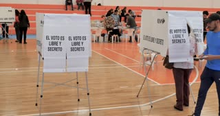 PATZCUARO, MICHOACAN, MEXICO - JULY 1, 2018 - Young Mexican man enters a voting booth to cast his ballot on election day voting for the next president of Mexico