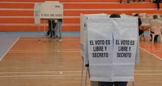 PATZCUARO, MICHOACAN, MEXICO - JULY 1, 2018 - Young Mexican man leaves a voting booth with his ballot for the next Mexican president on election day