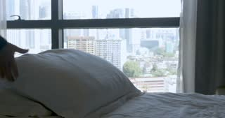 Person fluffing pillows on a bed with clean fresh linens with a urban city view from the bedroom