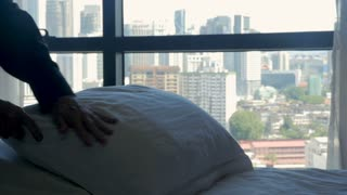 Person smoothing out pillows for a freshly made bed overlooking a modern city in a hotel room or fancy home in slow motion