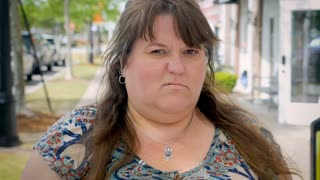 Pissed off angry mad bothered attractive obese woman standing outside giving the evil eye in a modern outdoor shopping mall