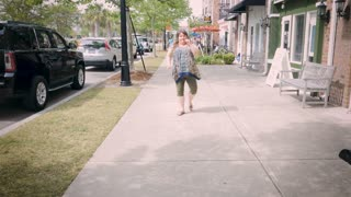 Plus size happy smiling model woman funky dancing on town sidewalk near shops in day