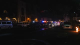 Police cars driving slowly down a street with their strobing blue and red rotating beacons and LED lights on the sidebar during Mexican Independence Day in Mexico at night