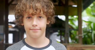 Portrait of a cute young 11 - 12 year old boy with curly hair smiling and looking at the camera