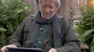 Portrait of a handsome healthy stylishly dressed elderly man in his 70s laughing and cracking up while holding a tablet sitting outside in his backyard