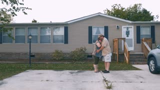 Portrait of a happy heavy couple hugging in front of a manufactured home and looking at the camera smiling - wide shot