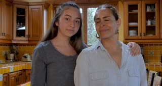 Portrait of a Latino mom and her teenage daughter smiling and looking at camera - push in handheld shot