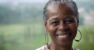 Portrait of a stunning African American woman in her 60s smiling at the camera outside