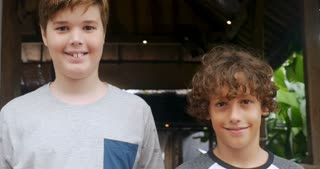 Portrait of a tall boy and short boy smiling and looking at the camera both at around 11 - 13 years of age