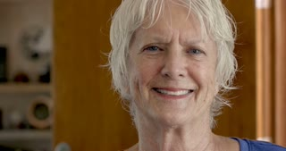 Portrait of an attractive 70 year old caucasian woman smiling and laughing in her home during the day looking at the camera