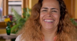 Portrait of an attractive hispanic woman smiling and laughing while looking at the camera