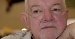 Portrait of an elderly senior man wearing nasal oxygen tubes talking out in public such as a restaurant or a party