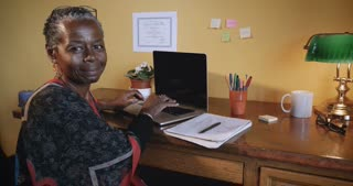 Portrait of beautiful vibrant successful mature African American woman smiling and happy sitting at work desk