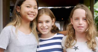 Portrait of diverse multi ethnic group of three young girls smiling and looking at the camera