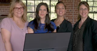 Portrait of four attractive successful professional entrepreneur women smiling behind a computer monitor in modern startup office - dolly shot