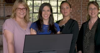 Portrait of four confident attractive successful business women smiling behind computer monitor