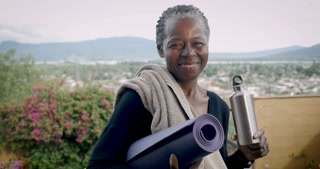 Portrait of happy elderly smiling African American woman over 60 holding yoga mat and water bottle - dolly shot