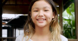 Portrait of young 11 - 12 year old cute happy Asian girl smiling and looking at the camera