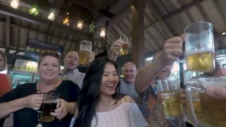 POV of a group of happy attractive people cheering and toasting with glasses of beer in a bar pub