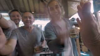 POV of a large group of happy smiling people giving someone a high five in a bar pub