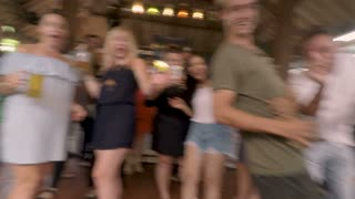 POV of a man celebrity walking into a bar with people greeting, kissing him, taking his photo, and cheering him