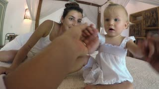 POV of a man helping his baby daughter stand up with his wife lying on the bed talking to the young one year old girl