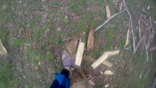 POV of a man splitting firewood with a maul wearing gloves to protect his hands