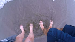 POV of the small waves crashing over a man and woman's bare feet standing in the sand